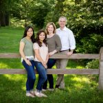 Family of 4 leaning on split rail fence in backyard for pictures