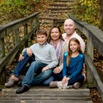family pictures posed sitting on wooden walking bridge