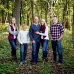 family pictures in woods family standing with blue jeans