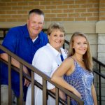 portrait of family in blues and whites with railing