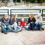 Four adults with one child gather next to the Cedar River in Waverly for family picture session