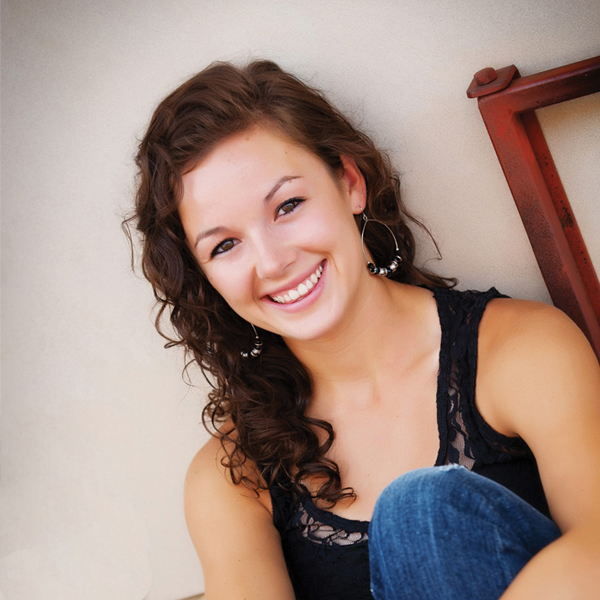 Senior Picture of girl sitting leaning against wall