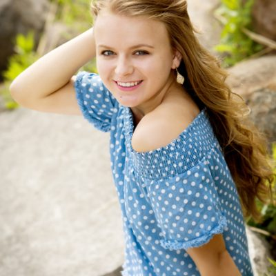 Senior girl wearing baby blue off the shoulder top with white polkadots hand on hand and laughing