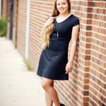 Senior Picture Gallery Girl with very long hair in short black with short sleeves leaning left shoulder on brick wall