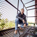 High school senior boy squatting on fire escape platform