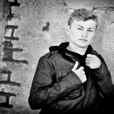 Senior Picture Gallery Waverly Cedar Falls Iowa Black & White photo boy in leather jacket leaning on brick wall Bo Studio 121