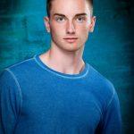 Handsome Waverly Shell Rock senior boy wearing turquoise shirt on turquoise background
