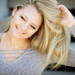 Senior Picture Gallery Blond senior girl with hand in hair head tilted and laughing