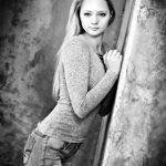 Black & White blonde girl leaning on concrete wall