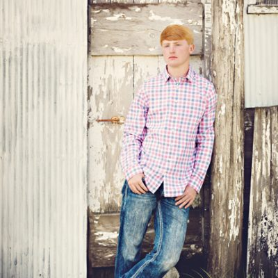 Red headed senior boy with thumbs in pockets leaning against wooden pole