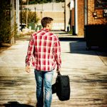 Guy walking down waverly iowa alley with guitar