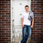 Tall senior boy with flannel shirt over shoulder leaning against white wooden door on brick building