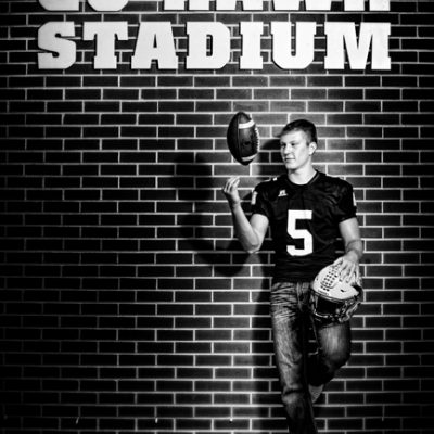 BW senior picture Boy spinning football leaning against brick wall
