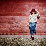 Cedar Falls high school senior girl wearing brimmed hat over eyes leaning on painted red brick wall