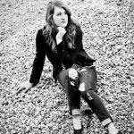 Girl sitting on gravel pile posing for senior pictures