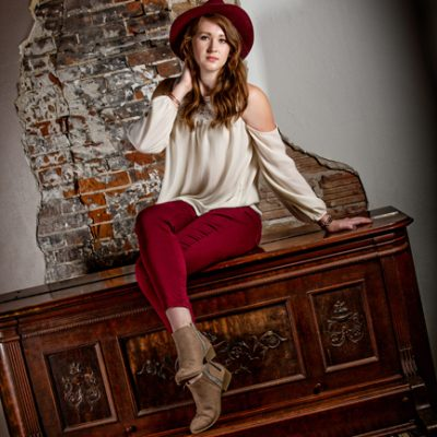 girl in rid hat sitting on piano