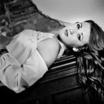 Senior Picture Gallery Waverly Cedar Falls Iowa B&W Senior picture girl with long brown hair laying on piano Waverly Iowa