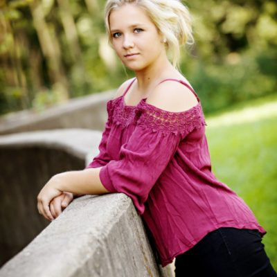 Cute blond girl with hair up leaning on cement wall with arms crossed