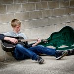 Senior guy playing guitar leaning against wall in Waverly Ia