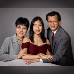 Asian family of three dressed in grey and burgundy formal clothing posed in photograph