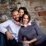 Young family portrait in studio on brick background