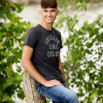 Grey t-shirt worn for senior pics by a boy leaning on wood post.