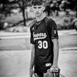 Sumner-Fredericksburg High School baseball jersey worn by senior boy holding baseball and glove