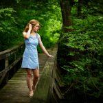 High school teenage girl in blue dress walking on wooden bridge in Waverly IA woods.
