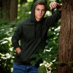 high school senior boy leaning against a tree wearing a green hoodie