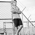 Black & White photo of senior boy wearing shorts leaning against chain link fence.